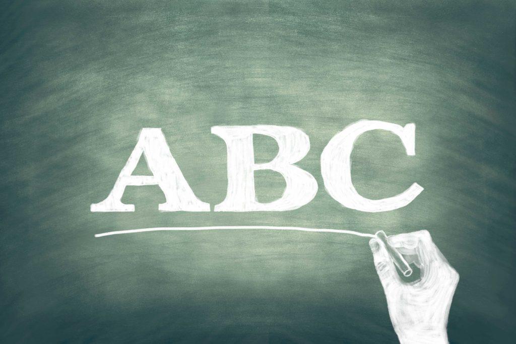 チョークでABCの文字を黒板に書く