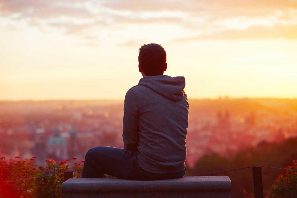 丘の上から夕日の街を見つめる男性
