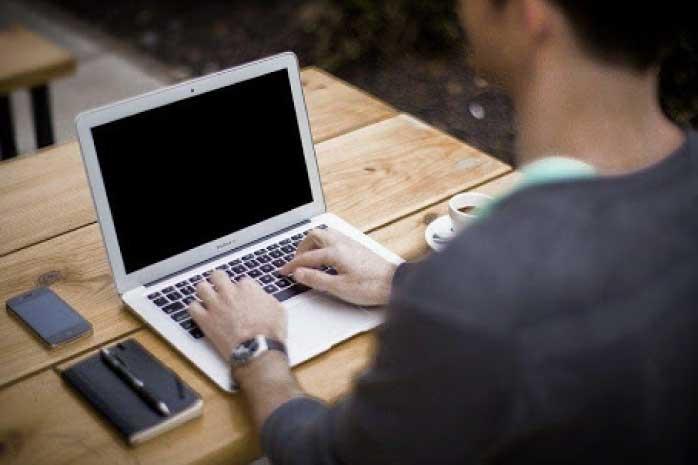 テーブルでパソコンをしている写真