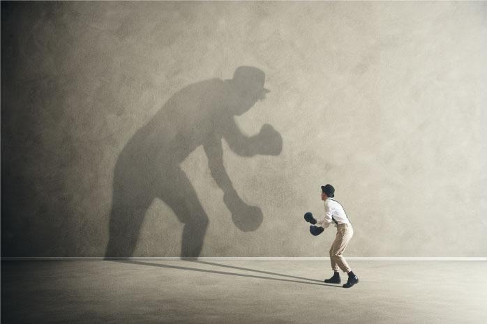 シルエットの自分とボクシングで向き合う男性の写真