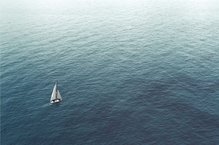 広大な海を一隻の船が渡ろうとしている写真
