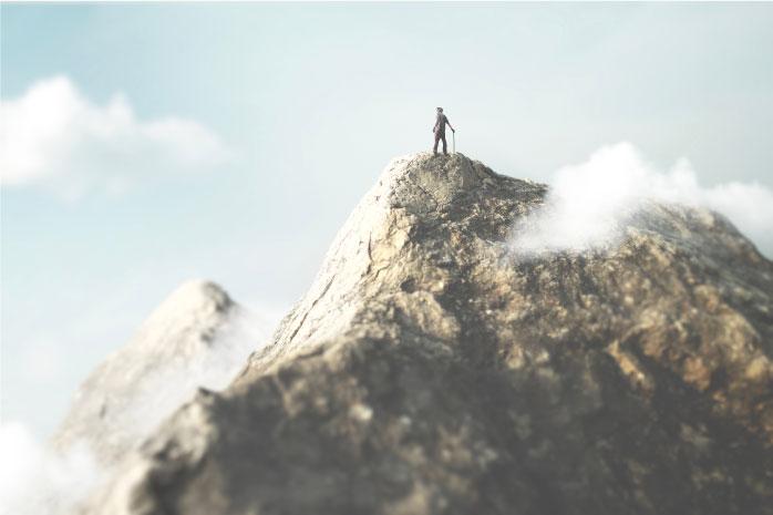 聳え立つ山の天辺に立つ人の写真