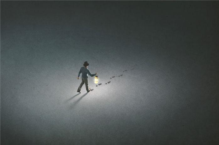 暗闇の中をランプをてらし歩く人の写真