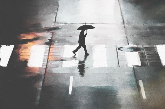 横断歩道を傘をさして歩く男性の写真