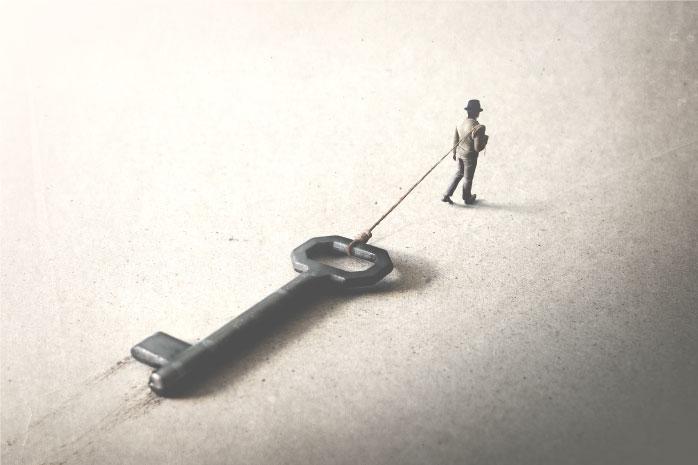 大きな鍵を引っ張っている男性の写真