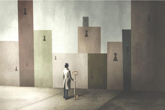 たくさんの鍵穴の前に立つ男性の写真