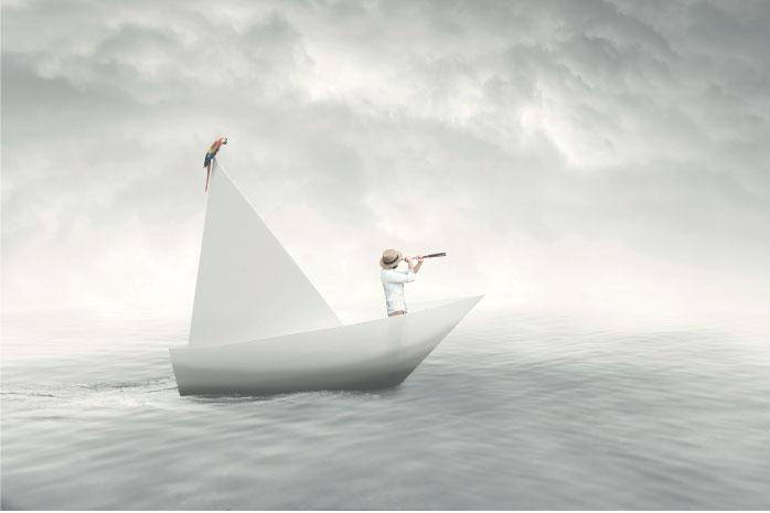 海の上に浮かぶ紙でできた船から望遠鏡で眺めている男性の写真