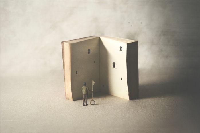 大きな本に沢山の鍵穴が空いている写真