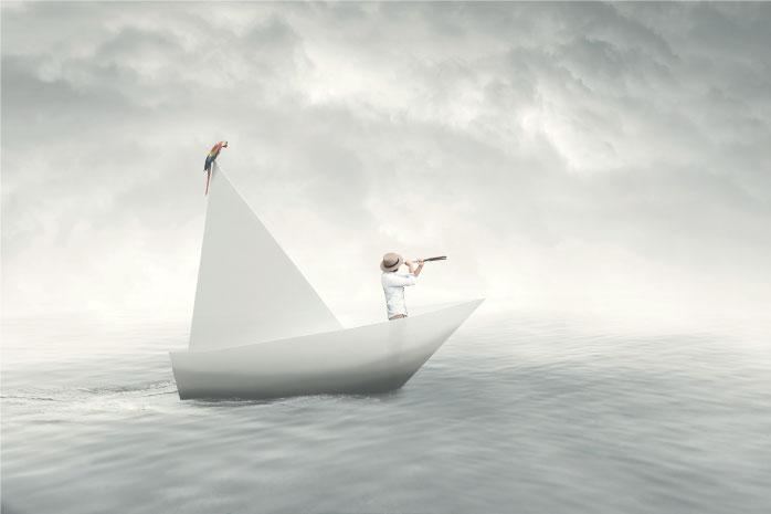 折り紙のボートから双眼鏡で海を見ている男性の写真
