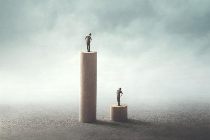 長い柱と短い柱の上に立っている男性の写真