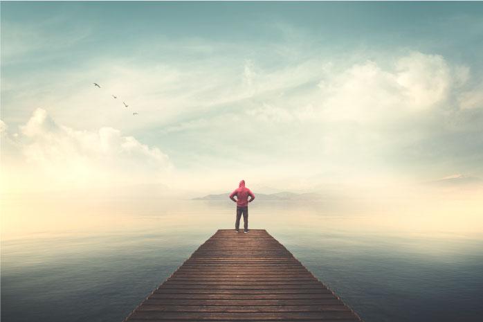 広がる海の突き出した橋の先端に立っている人の写真