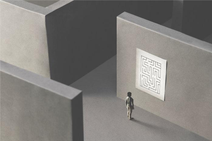 迷路の壁に貼られた地図を確かめている人の写真