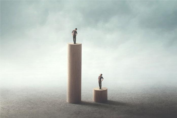 高い柱と短い柱の上に立っている人の写真
