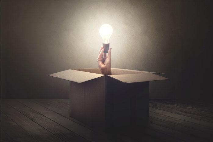 段ボールから電球をもった手が出ている写真