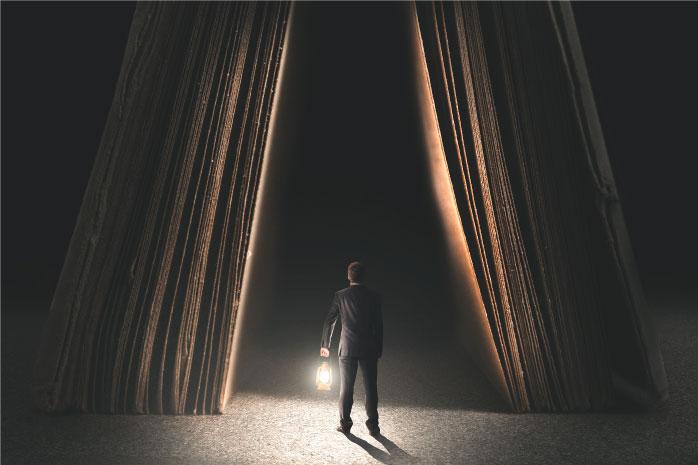 ランプをもった男性が暗闇の中に入っていく写真