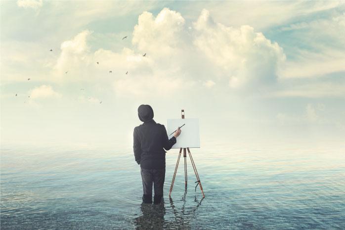 海の中でスーツを着た男性がキャンバスに向かっている写真